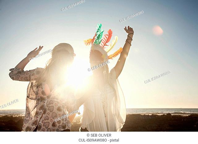 Young women wearing feather headdress arms raised dancing in sunlight