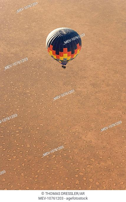 Hot-air balloon above a sandy plain at the edge of the Namib Desert. The so-called 'Fairy Circles' are circular patches without any vegetation which according...