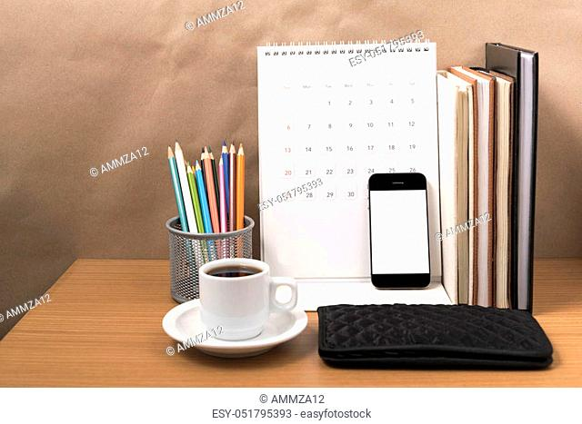 office desk: coffee with phone, wallet, calendar, color pencil box, stack of book on wood background