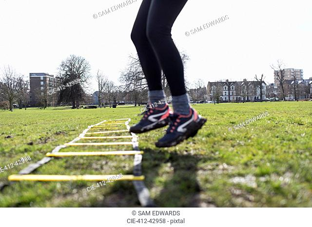 Woman using exercising ladder in park