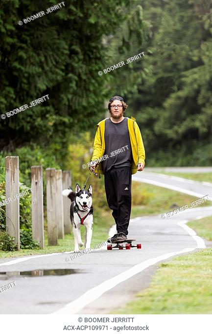 A skateboarder runs his Husky dog along the pedestrian walkway that runs alongside hwy 4 outside of Tofino, Tofino, Vancouver Island, British Columbia, Canada