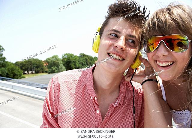 Two teenage friends with headphones outdoors