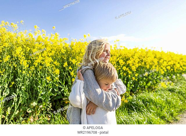 Happy girl embracing brother at rapeseed field