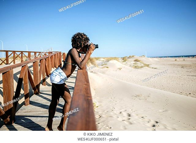 Young woman taking photos on the beach