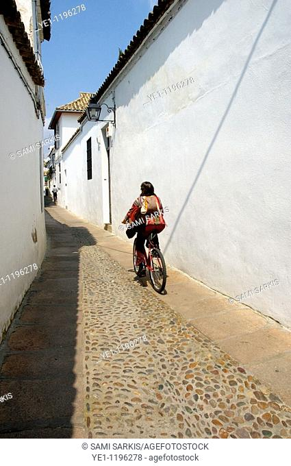View of woman riding a bike through a cobbled alley in the Juderia Quarter, Cordoba, Andalusia, Spain