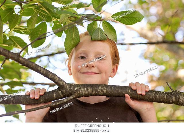 Portrait of Caucasian girl holding tree branch