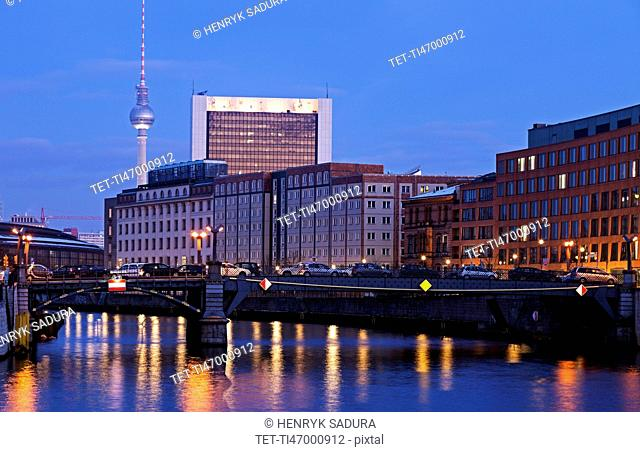 Illuminated riverfront skyline with television tower