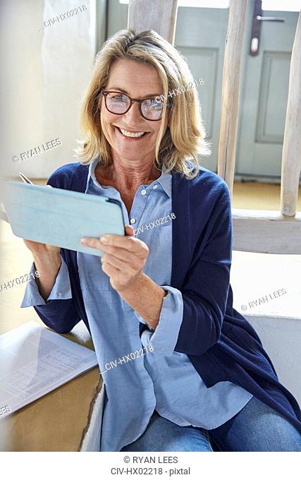Portrait smiling senior woman using digital tablet