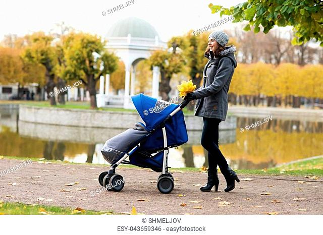 Mother walking with a baby pram (stroller, carriage) in the park. Autumn nature background. Love and family concept