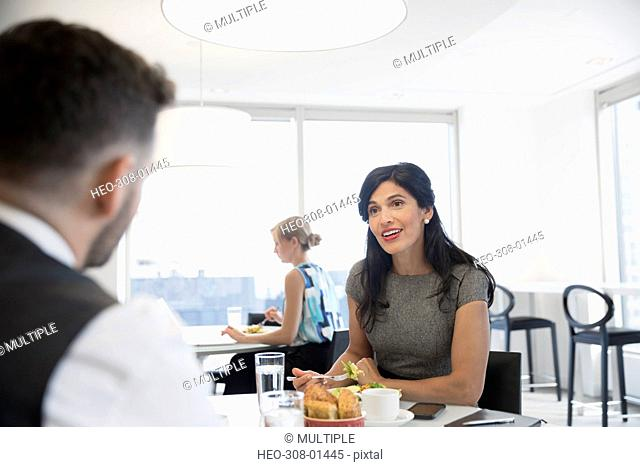 Smiling businesswoman and businessman eating lunch in office cafeteria
