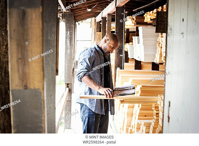 Man standing in a lumber yard, holding a folder, checking wood