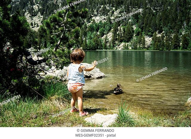 Spain, Little girl standing at mountain lake waving at a duck