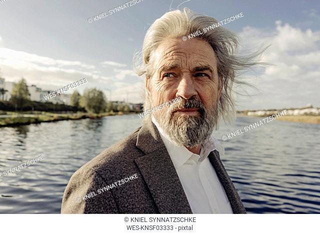 Portrait of serious senior man at a lake
