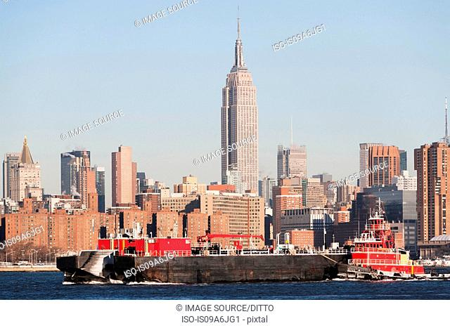 Barge floating by New York City skyline