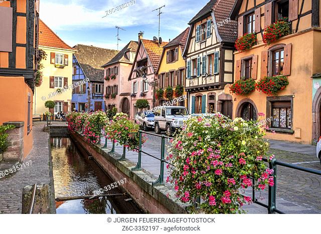 flower decorated brook and old timbered houses with carving, village Ribeauvillé, Alsace, France, location of the Wine Route