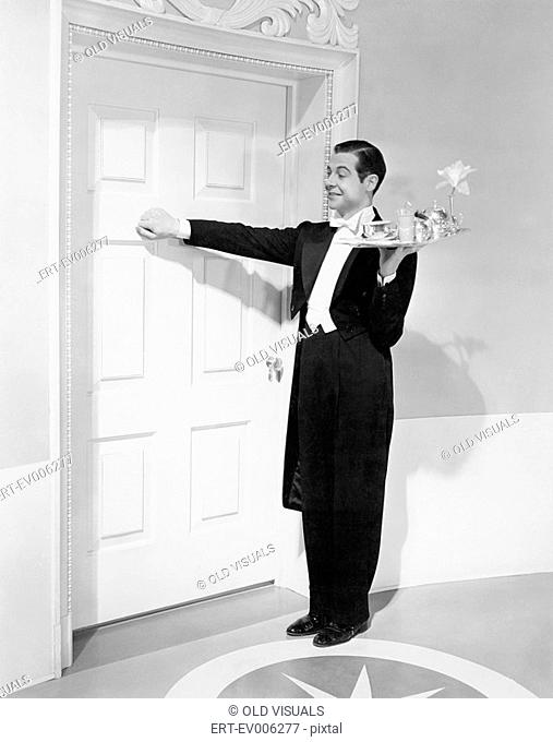 Waiter with tray knocking on a door All persons depicted are not longer living and no estate exists Supplier warranties that there will be no model release...