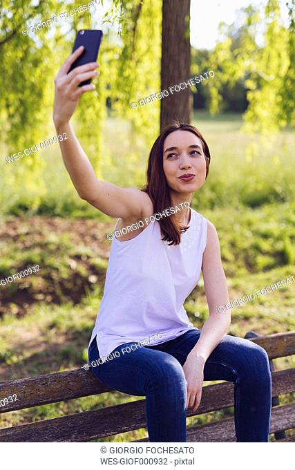 Woman taking a selfie while sitting a bench at the park