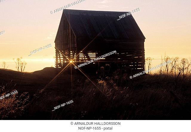 Sunset behind the silhouette of a barn