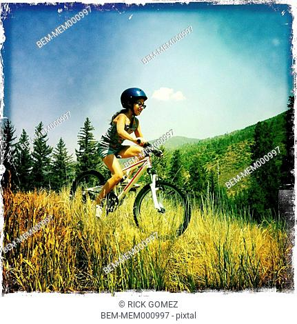 Hispanic girl riding mountain bike in tall grass