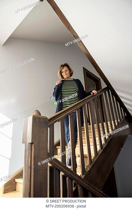 Senior woman wearing winter coat moving down on a staircase, Munich, Bavaria, Germany