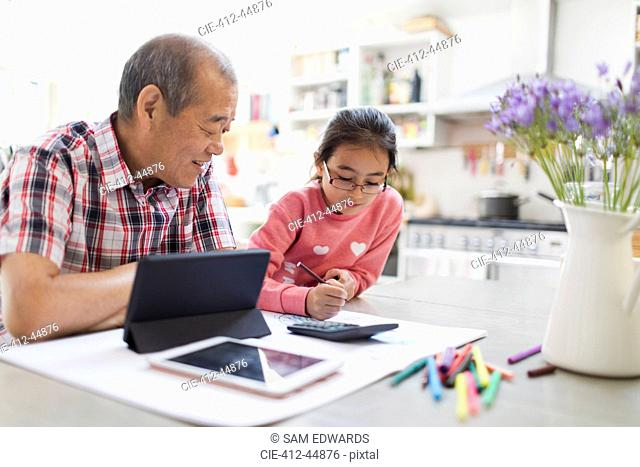 Grandfather and granddaughter coloring and using digital tablet in kitchen