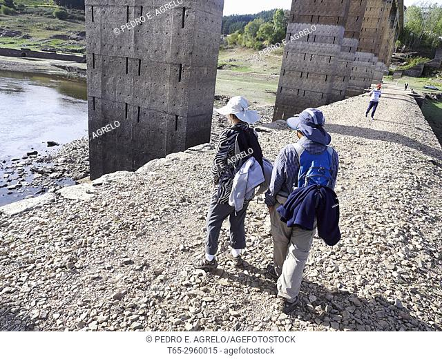 Pilgrims visiting an old bridge in the village of Portomarin, Lugo French Route of the Way. The drought in the reservoir allows to see constructions