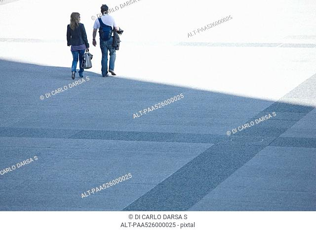Couple walking together across public square