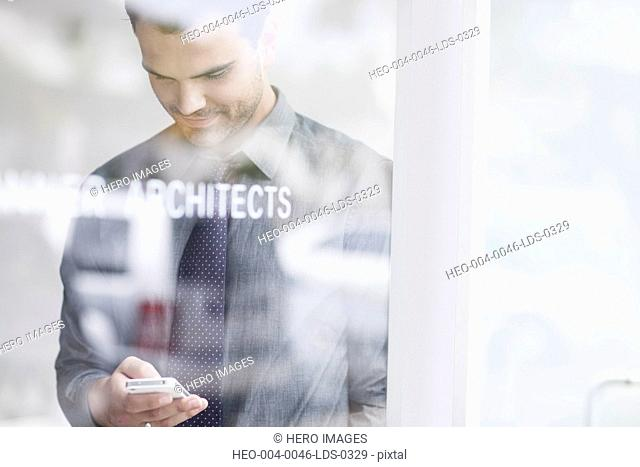 young architect texing on smartphone