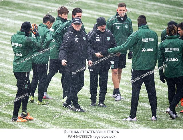 New head coach of German Bundesliga soccer club Hannover 96, Thomas Schaaf (4-L), and assistant coach Matthias Hoererbach (5-L) stand on the pitch with team...