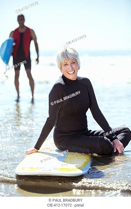 Portrait of senior woman on surfboard at beach