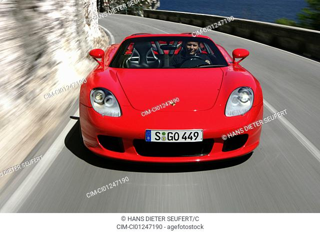 Car, Porsche Carrera GT, model year 2005-, red, Convertible, open top, driving, diagonal from the front, frontal view, country road, landsapprox