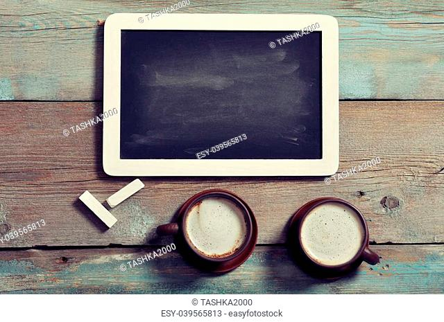 Small wooden framed blackboard with two cups of coffee on wooden background