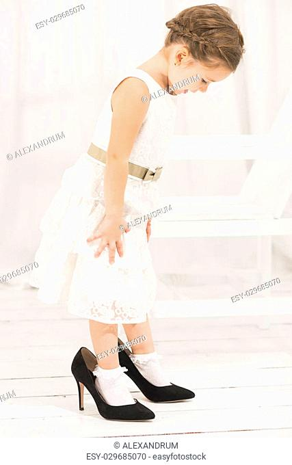 Adorable cute caucasian girl wearing white dress and black high heel shoes. Cute little girl trying to walk with big high heel shoes