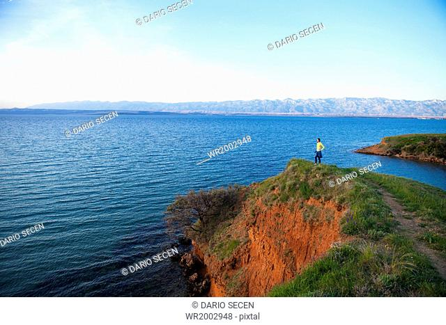 Young woman on cliff looking out at sea