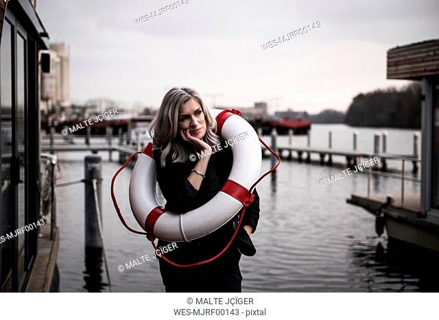 Businesswoman standing on a houseboat, looking worried, with lifesaver around