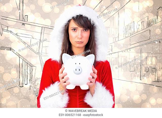 Composite image of sad festive woman holding a piggy bank in her hands