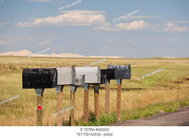 USA, South Dakota, Row of rural mailboxes on roadside in Buffalo Gap National Grasslands