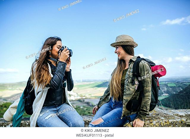 Two happy young women on a trip taking a photo