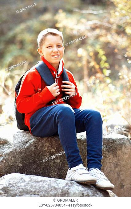 Happy smiling hiker boy with backpack in forest. Dressed in red sweatshirt