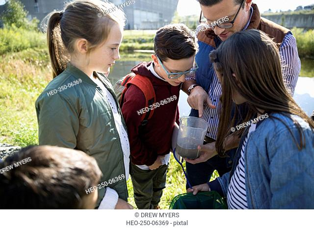Science teacher and students examining water field trip
