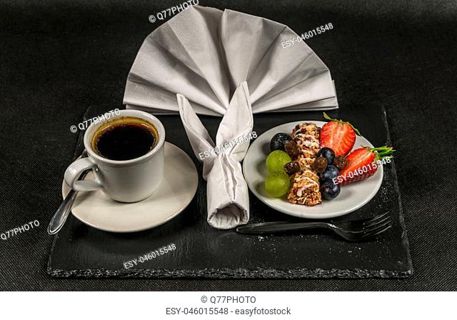 black coffee in white cup, healthy, energetic breakfast, bar whole grain, grapes, strawberries and blueberries, napkin, sweet set