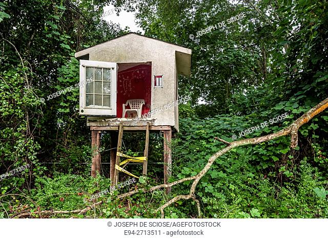 An elevated children's play house nestled among trees and kudzu vine in a back yard in the country, Alabama, USA