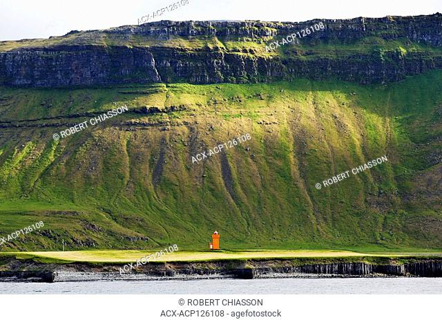 Steep mountainside towering above an orange lighthouse northwest of Grundarfjordur on the Snaefellsnes Peninsula, Iceland