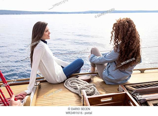 Two women hanging feet over the edge of yacht