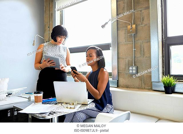 Young woman sitting, looking at smartphone, colleague standing beside her