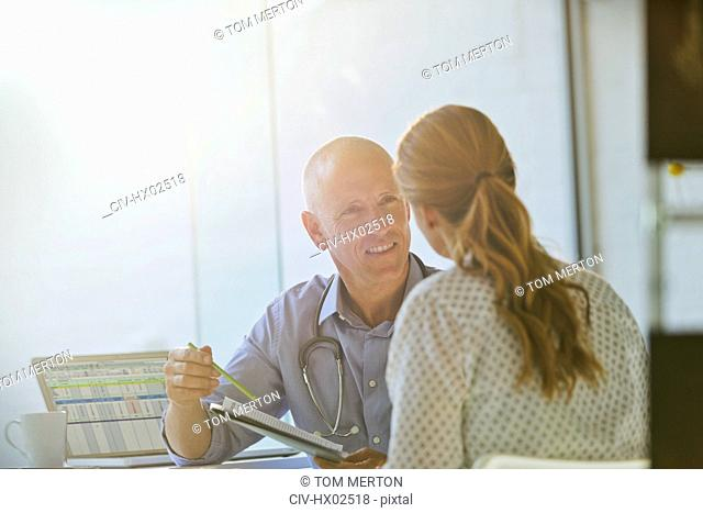 Male doctor discussing brochure with female patient in doctor's office