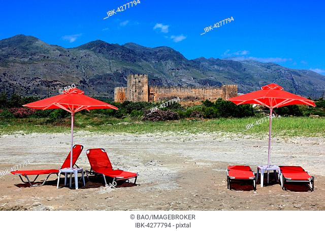 Red sun loungers and parasols in front of Frangokastello castle, Crete, Greece