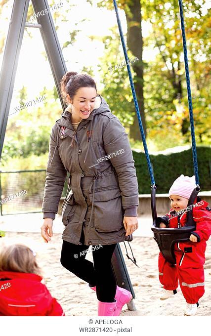 Happy woman looking at daughter enjoying on swing at park
