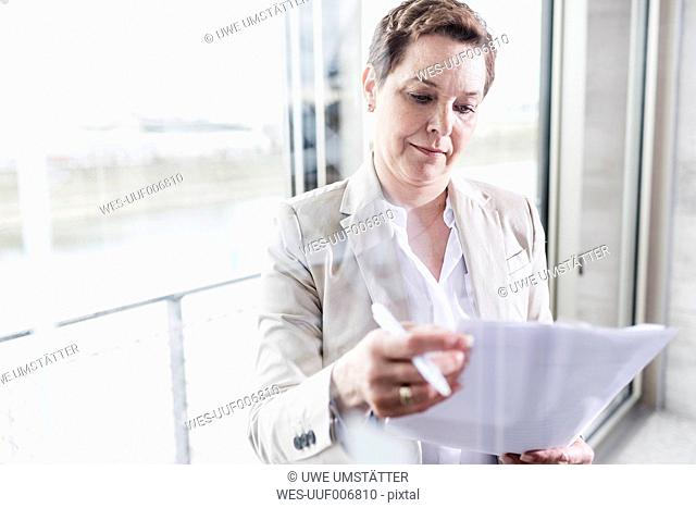 Businesswoman at the window reading document
