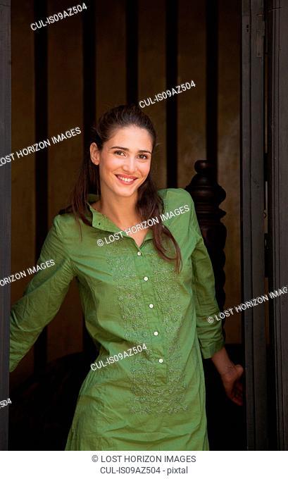 Woman in doorway looking at camera smiling, Marrakesh, Morocco